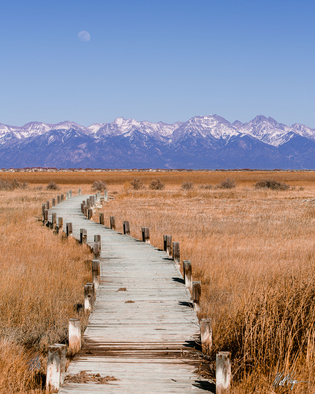 This bridge over marshy swap in the San Luis Valley leads the viewer to the towering Sangre de Cristo Mountains to the east as...