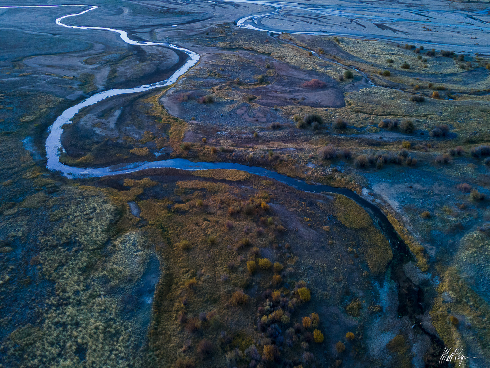 A small stream snakes through tall grasses and willow shrubs into a lake in Colorado in early morning autumn light. Photo ©...
