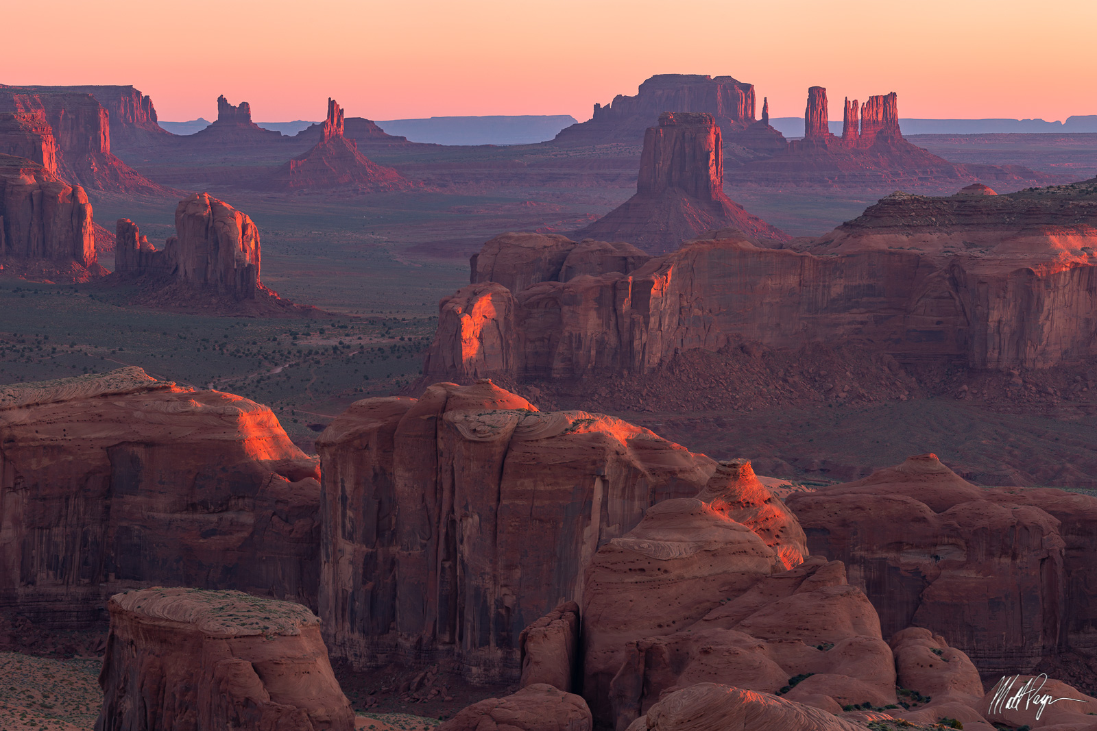 This grand scenic landscape photograph features an incredible view of the iconic sandstone formations in Monument Valley from...
