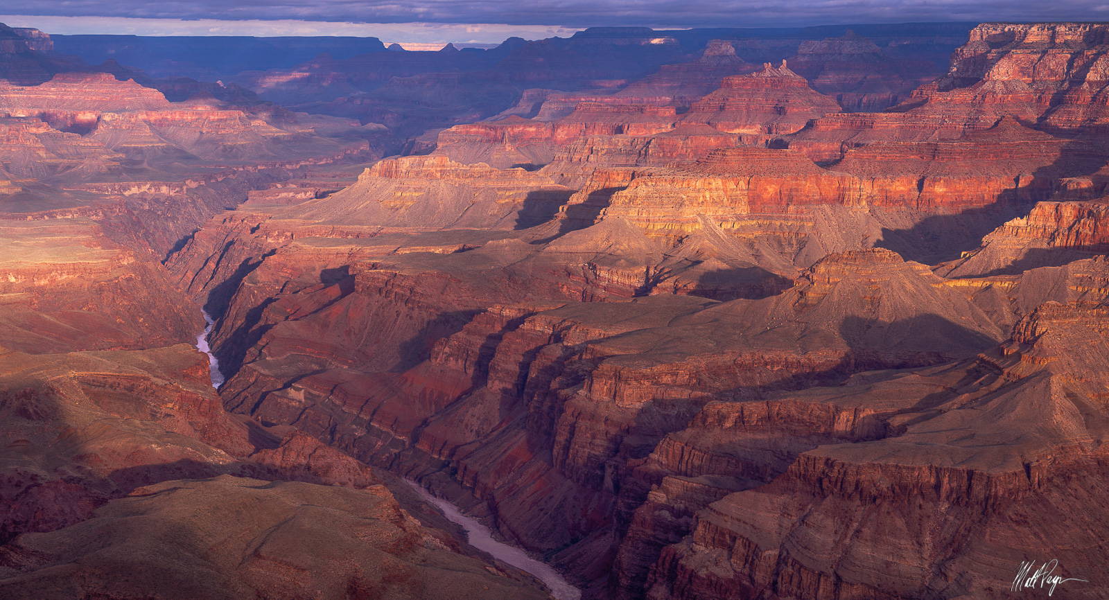 Early light illuminates a variety of layers in the Grand Canyon. The Colorado River carves out a line below - the roar of the...