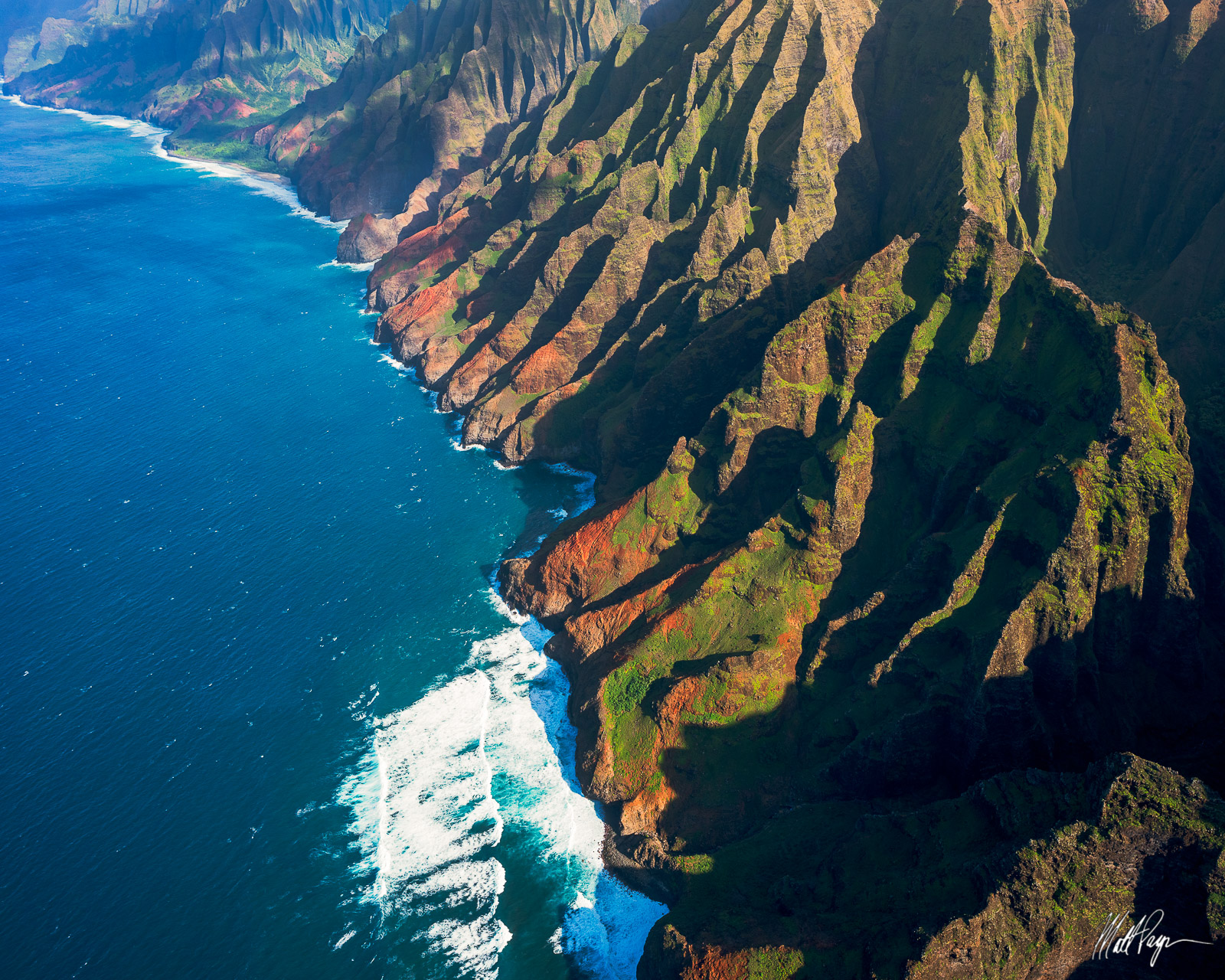 Late afternoon sun casts amazing light across the rugged Na Pali Coastline of Kauai as seen from a helicopter. The blue ocean...