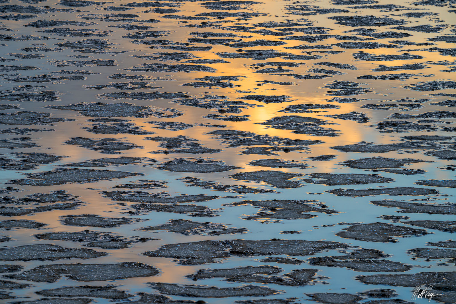 Cracks in the mud tiles found in the Alvord Desert of Oregon reflect the skies tones of orange and blue at sunset. Photo © copyright...