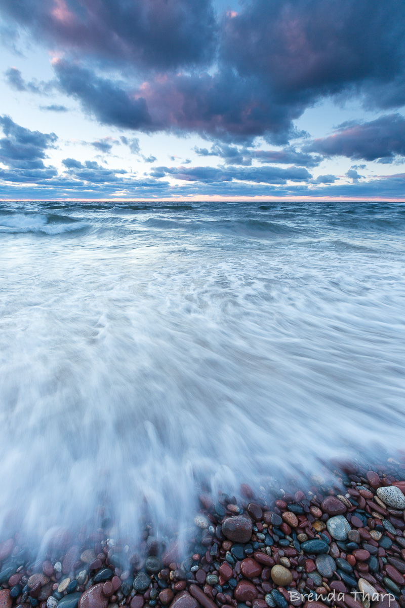 Wind-pushed water rushes the  shore of Lake Superior, Michigan.