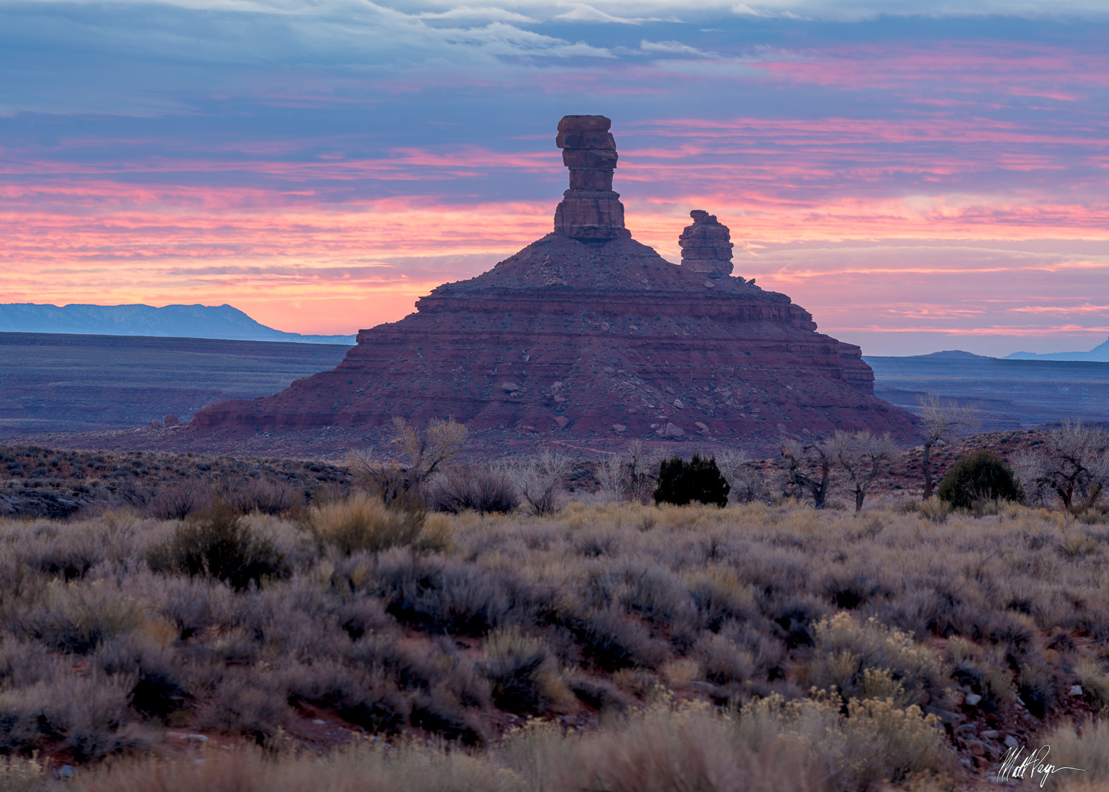 """Pastel sunrise colors illuminate clouds over the winter desert of Utah. These two rock features are known as """"The Rooster"""" and..."""