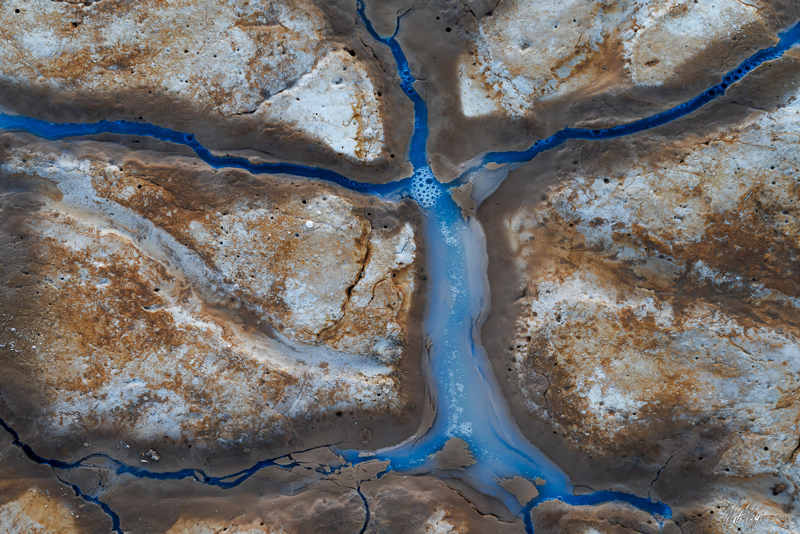 Water fills the tiles of mud on the desert floor and reflects the blue skies above, creating an effect that looks almost like...